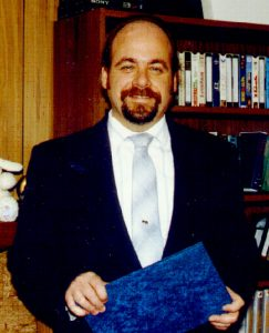 kevin-f-montague-in-suit-and-tie-holding-blue-folder